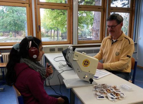 Dieter Schneider von der KKH beim Hörtest mit einer Schülerin