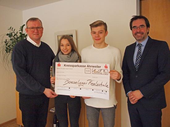 Greta Golly und Jan-Patrick Artz mit ihrem Schulleiter Klaus Dünker bei der Scheckübergabe an Bürgermeister Achim Juchem