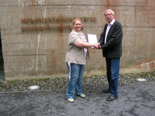 Heike Fournier übergibt ihre Examensarbeit Dr. Wilbert Herschbach, dem Leiter der Dokumentationsstätte