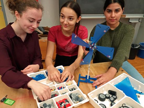 Monja, Zeyneb und Slava mit dem LEGO-Modell einer Windkraftanlage