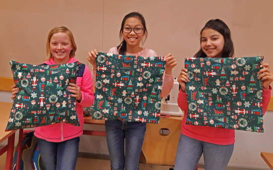 Katy, Ha My und Azita aus der Näh-AG mit ihrem ersten kreativen Werk - einer weihnachtlichen Kissenhülle